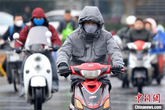 强冷空气来袭,25日早晨,南京市民全副武装出行。