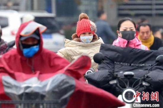 25日,强冷空气袭击江苏,市民全副武装出行。