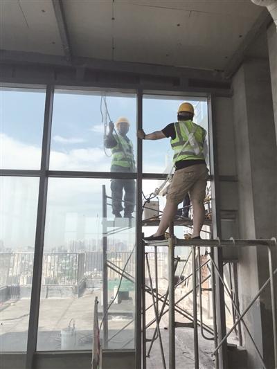 工作人员正在实验性拆除内侧玻璃