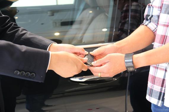 销售经理为陈先生递上期盼已久的车钥匙