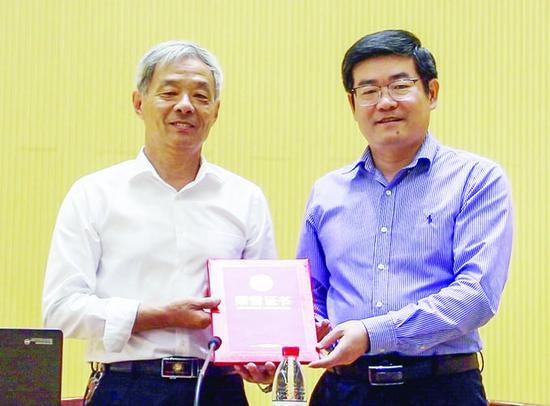 学校党委副书记倪永宏为顾秋亮(左)颁发校外辅导员聘书