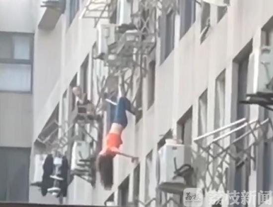 """扬州女子""""倒挂""""8楼晾衣架 众邻居拼命施救"""