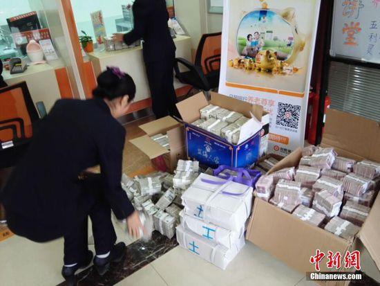 11月19日,山东省日照市日照银行内,工作人员在清点40万元零钱。
