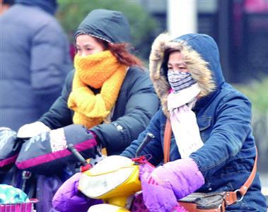 昨天低温潮湿,骑车人穿戴严实抵御寒风。金陵晚报记者 刘鹏 摄