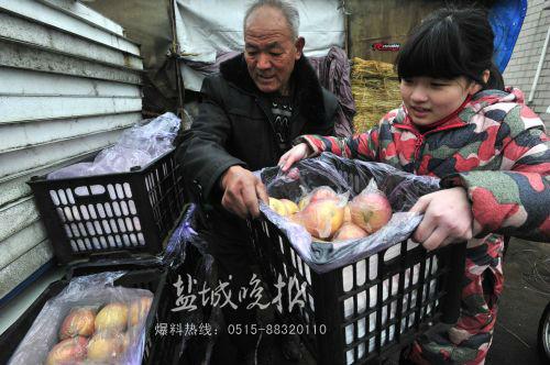 许多看到《盐城晚报》报道的读者前来购买苹果。跟着妈妈来买苹果的市实验小学六年级学生周澍忙着帮李大爷搬运苹果箱。
