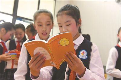 图为孩子们在仪式现场阅读活动赠书。 新华报业视觉中心记者 邵 丹摄