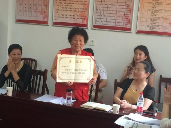 """""""红马甲""""义工队队长王培华展示了""""全国老有所为楷模""""荣誉证书"""