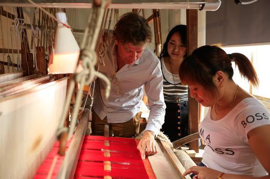 托马斯与女织工探讨工艺。