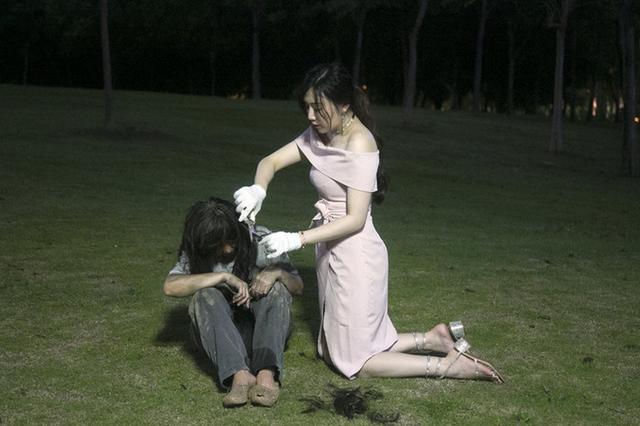 美女跪地为流浪者剪头发 网友质疑炒作