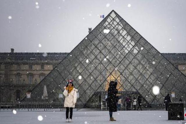 资料图片:巴黎降雪,游客在卢浮宫前拍照。