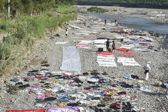 台风过后 浙江台州村民溪边晾晒衣被