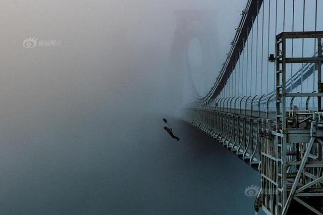 坠入迷雾!英摄影师抓拍牛人桥上定点跳伞瞬间