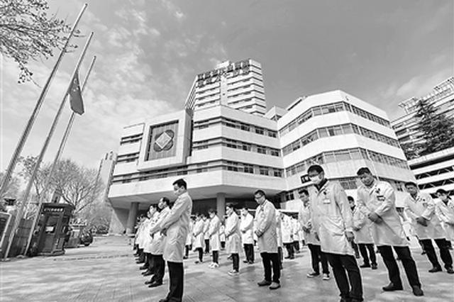 """4日,江苏省人民医院八十余名医护人员,包括驰援武汉一线刚刚解除隔离的""""白衣战士""""肃立默哀,悼念抗疫烈士和逝世同胞。 本报记者 余 萍摄"""