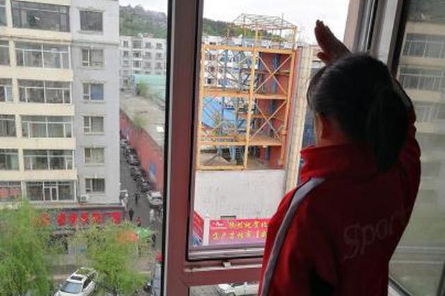 崔佳桐站在窗口向防疫卡点的老师敬礼 陈丽英供图