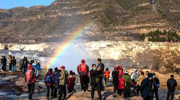 壶口瀑布巨冰伴彩虹吸引游客观赏