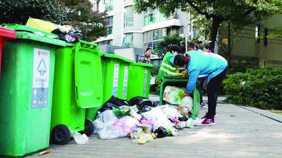 在银城东苑小区,物业人员将垃圾桶倒空,对垃圾进行二次分拣