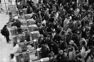 2月10日,旅客在南京火车站候车厅排队检票乘车。   苏阳 摄 视觉江苏网供图