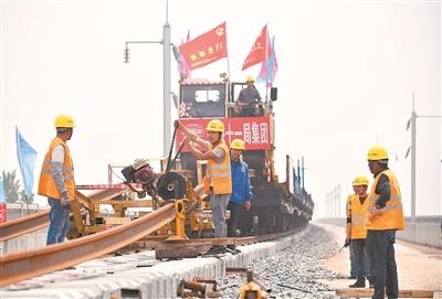 23日,建设者在徐州市贾汪区大湖村后马庄特大桥上铺钢轨。 郑绪军摄视觉江苏网供图
