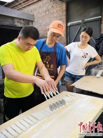 任晓猛、任文亚夫妻正在自家租住的小院里教授学员如何切面。中国青年报·中国青年网记者 邢婷/摄