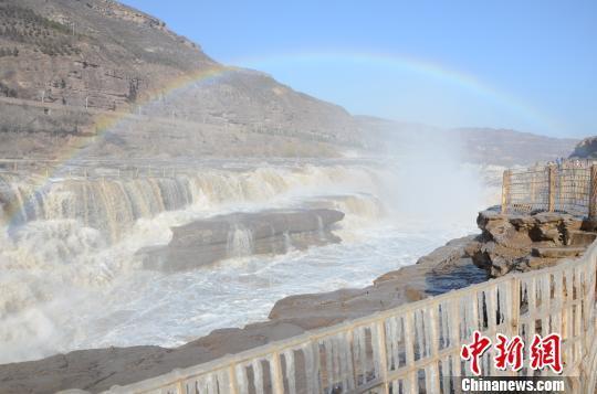 小雪时节,黄河壶口瀑布出现冰挂,天空中伴有一道彩虹。