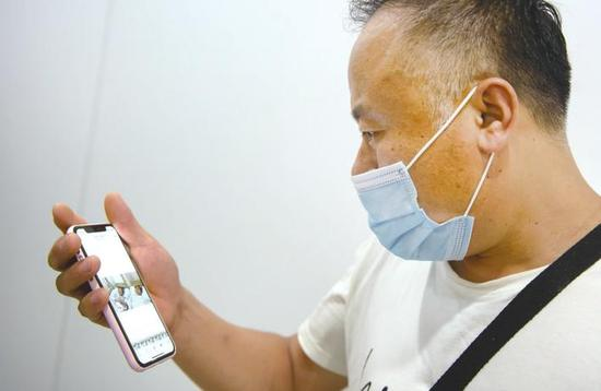 小桐父亲通过记者手机观看母女见面视频