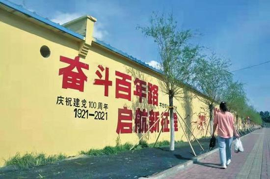 吉林市船营区新生街,市民走过文化墙。 姜岸松 摄