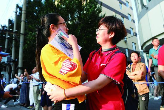 在东北师范大学附属中学考点,老师为完成考试的学生送上拥抱。 孙建一 摄