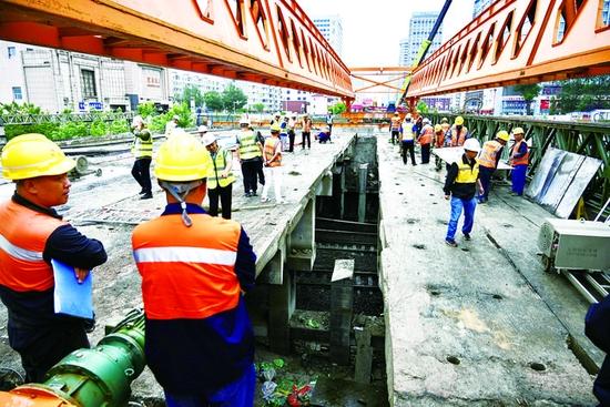 施工现场紧张有序,工作人员移除已经切割的桥梁。赵滨 摄