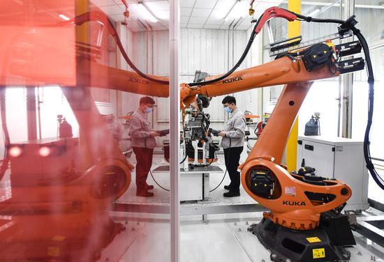 金涛在车间内操纵焊接机器人进行焊接作业(4月22日摄)。