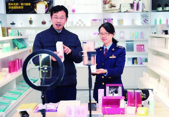 2020年12月10日,在浙江湖州美妆小镇党群服务中心,化妆品行业专家(左)和化妆品行业监管所工作人员通过网络直播开展专项宣传培训。(新华社发)