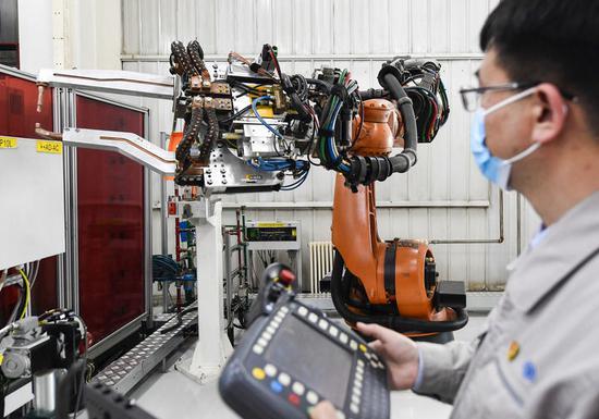 金涛在车间内对焊接机器人进行检测(4月22日摄)。