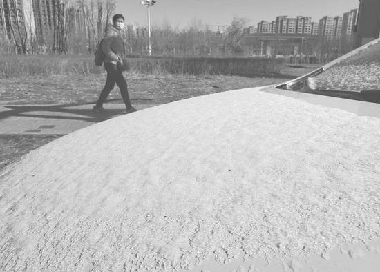 气温下降,4月13日清晨停靠在路边的汽车上覆盖了一层冰雪