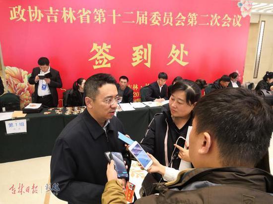 省政协委员完成报到程序后,接受记者的采访。