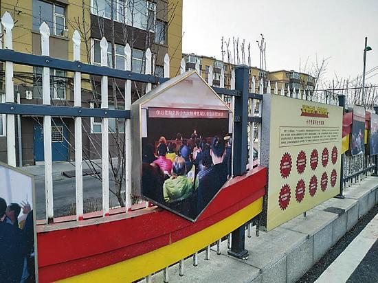 街道两边的栅栏和围墙上贴满了宣传画。