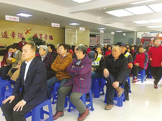 长山花园社区居民党员在看全国两会报道。