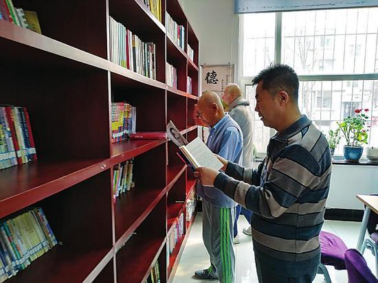 银山路社区的居民在图书室看书看报。