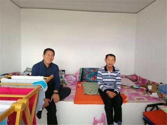 张赤旗(左)去看望下肢瘫痪的贫困村民