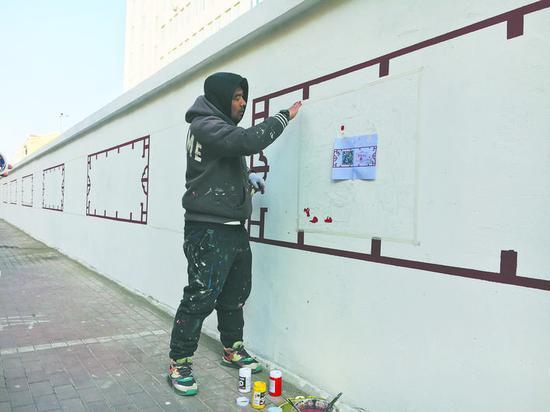 王宏宇在幸福嘉园的围墙上画画