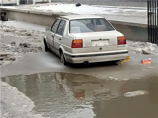 延吉一辆私家车被冻冰里 物业使用设备挪车