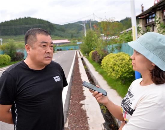 记者采访三脚窝石村驻村第一书记陈磊