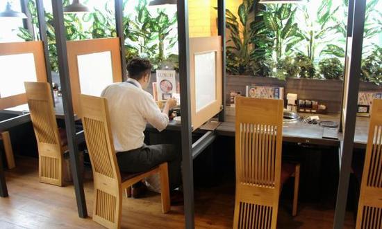 当地时间2017年6月,日本福冈,一名男子在一家餐馆的单人隔间吃饭。近几年来,日本越来越的餐馆都设立了单人隔间,甚至还出现了单人KTV。