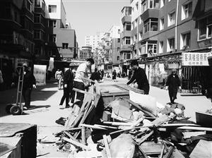 拆违工人在缓台上用木板搭建垃圾道运送建筑垃圾。