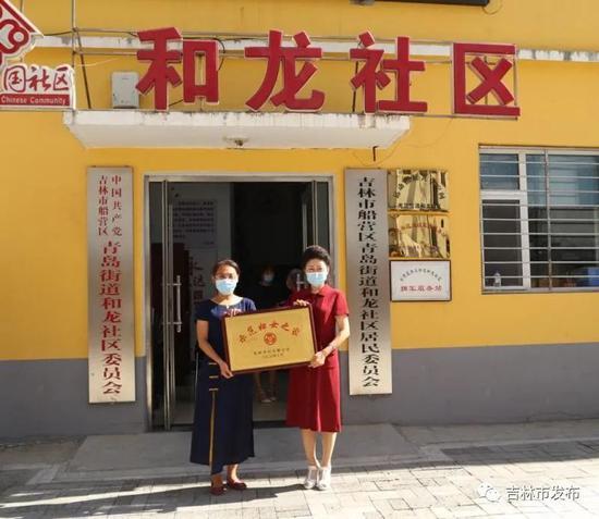 """吉林市妇联负责人(右)向社区授予了示范""""妇女之家""""奖牌"""