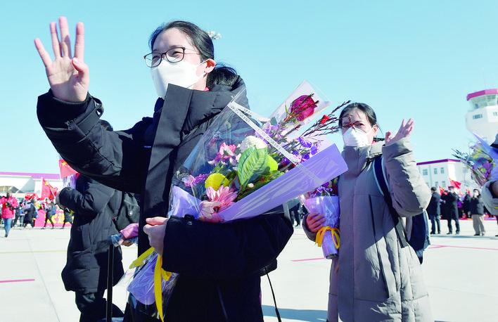 28日,医疗队队员向欢迎队伍挥手致意。 当日,吉林省支援湖北医疗队第三批返回的医护人员飞抵长白山机场。 (新华社发)