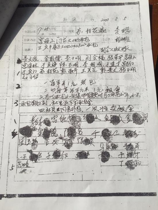 """造假的会议记录,社员不同意外包的""""不""""字被勾掉。 新京报记者 赵凯迪 摄"""