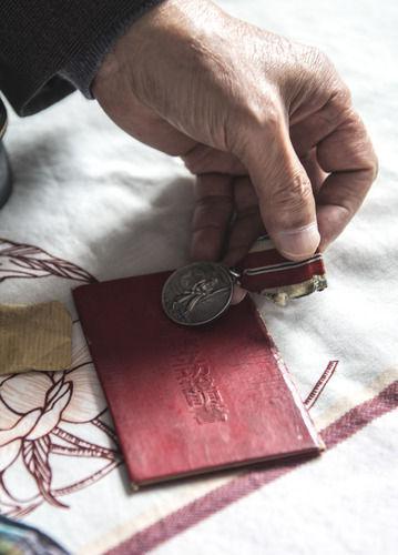 在吉林省通化市,志愿军老战士孙泰镐展示纪念章和立功证明书(9月29日摄)。