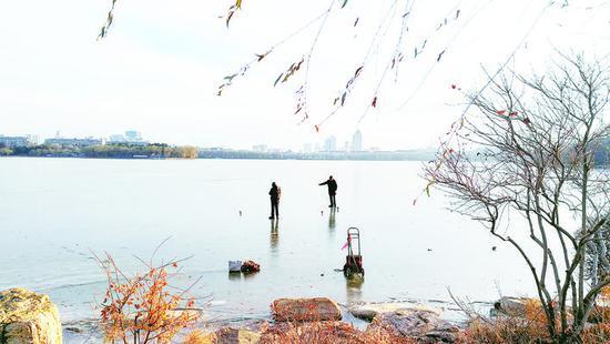 两位市民在冰面上玩陀螺,真危险。 李成伟 摄