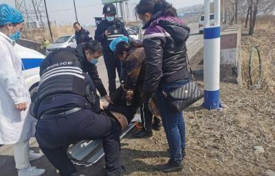 民警帮助医护人员将女子抬上担架