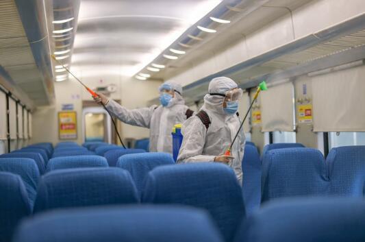 防疫员姜涛(右)在硬座车厢内喷洒消毒水。新华社记者 张楠 摄