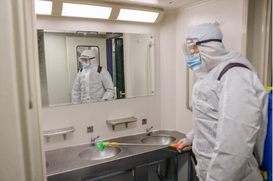 防疫员姜涛向车厢洗手池喷洒消毒水。新华社记者 张楠 摄
